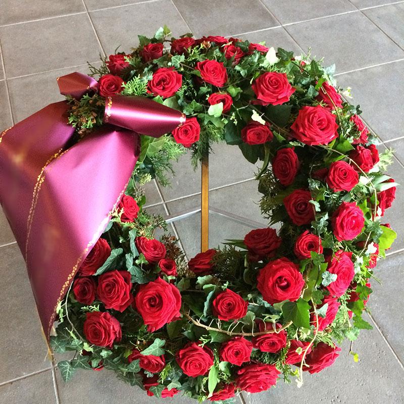 Trauerkranz mit roten Rosen, gemischtem Grün und Efeuranken umspielt.