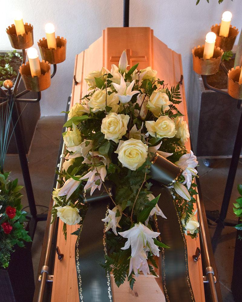 Sargschmuck länglich mit weißen Rosen, weißen Lilien und mit Efeuranken umspielt.