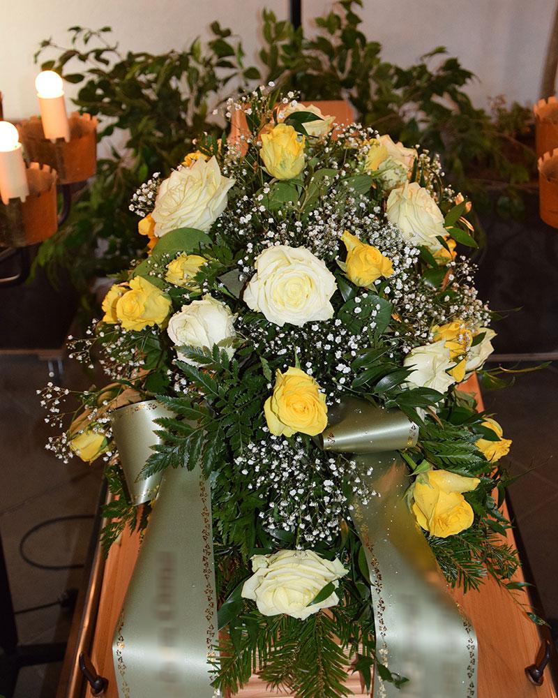 Sargschmuck länglich mit weißen und gelben Rosen, gefüllt mit weißem Schleierkraut.