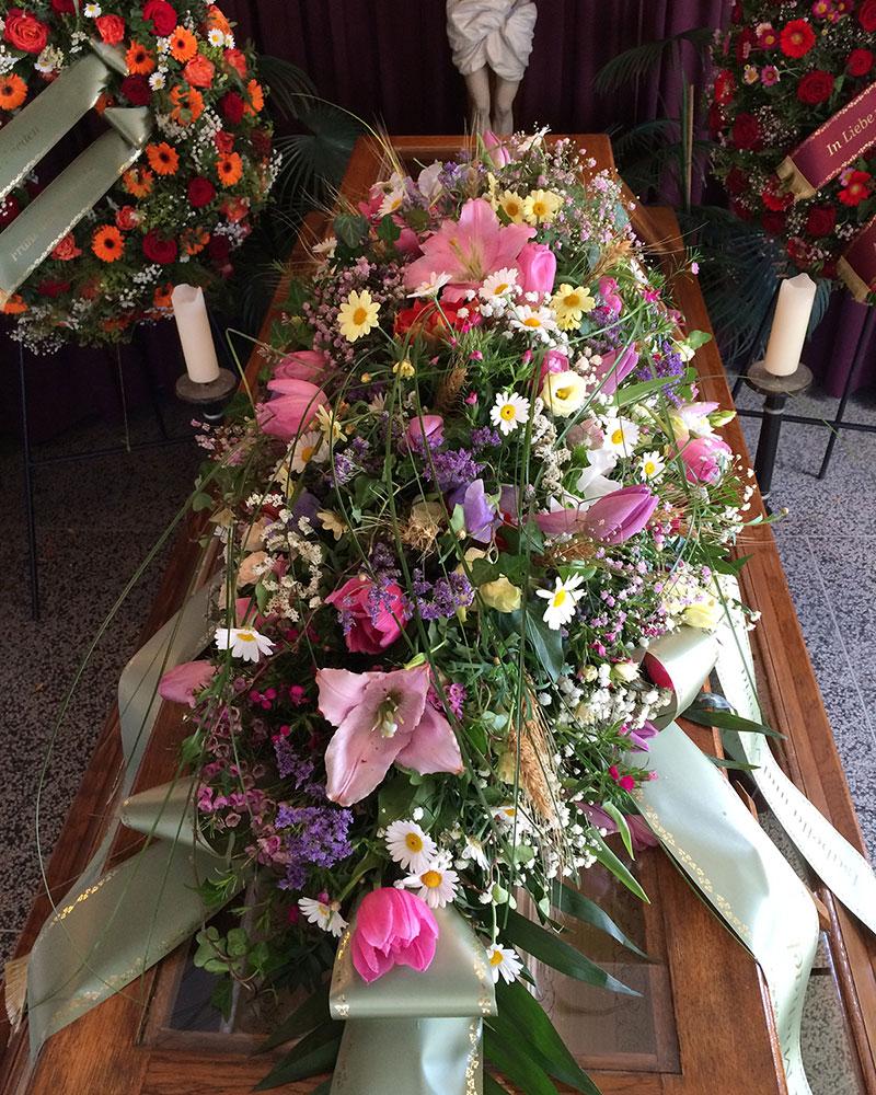 Buntes Sargbukett mit saisonalen Blumen.