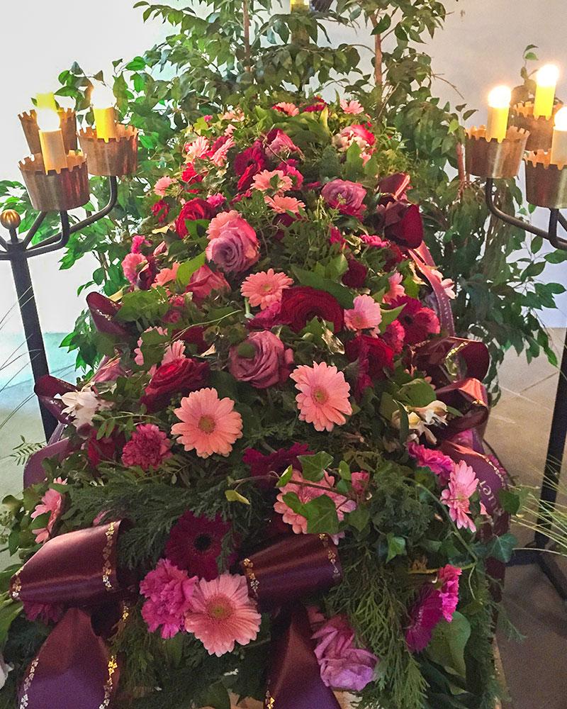 Sargdecke mit rosa Germini und roten Rosen.