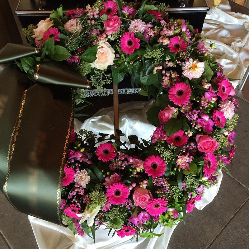 Trauerkranz mit pinken Germini, rosa Rosen, gefüllt mit rosa Schneebeeren.
