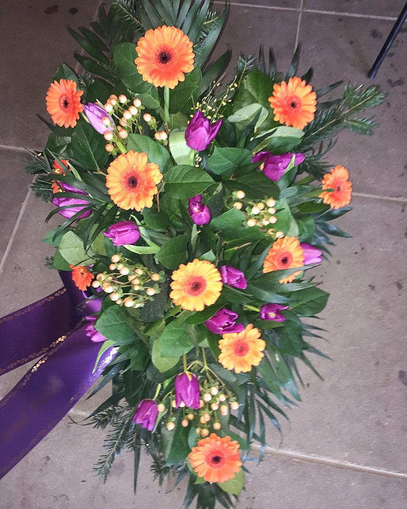 Frischblumenbukett in Tropfform mit orangen Germini, lila Tulpen und creme Hypericum