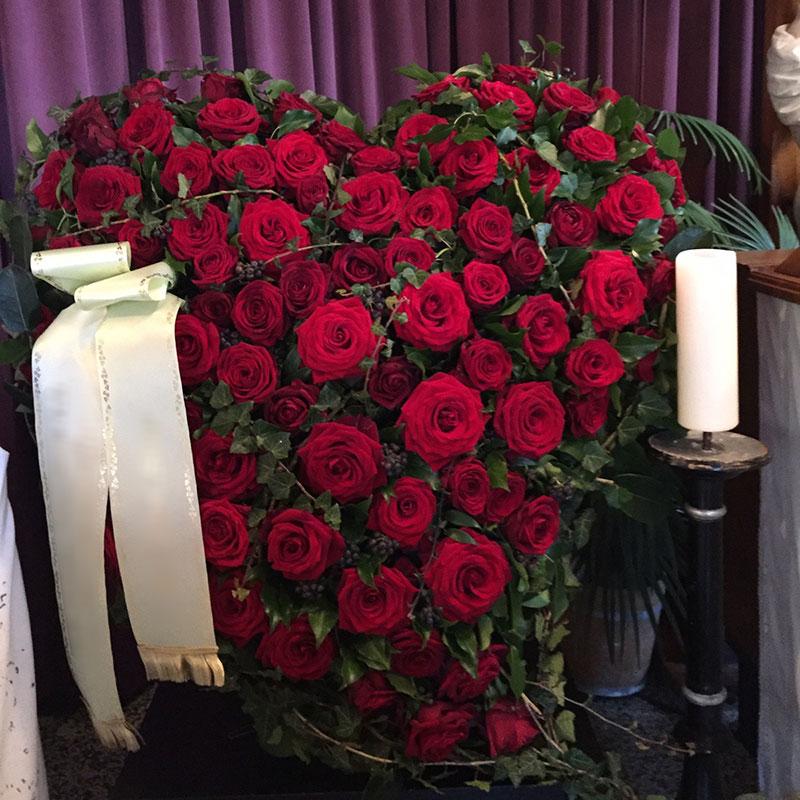 Trauerherz mit roten Rosen.