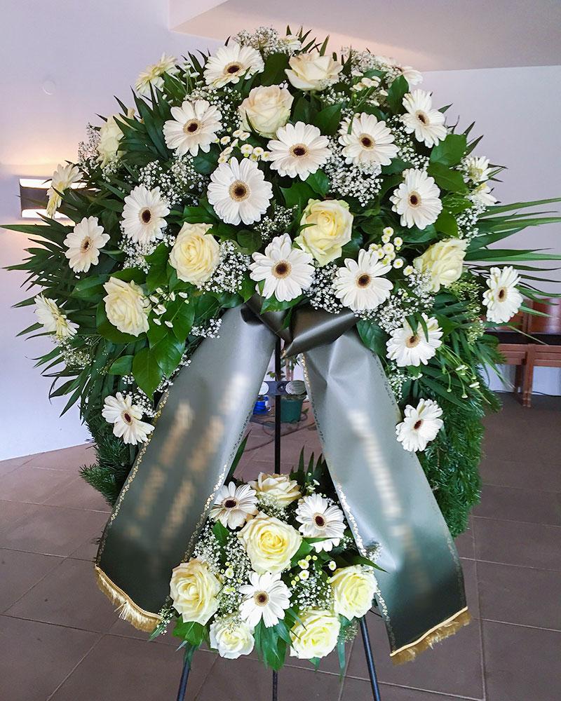 Trauerkranz mit weißen Gerbera, weißen Rosen, gefüllt mit Schleierkraut.
