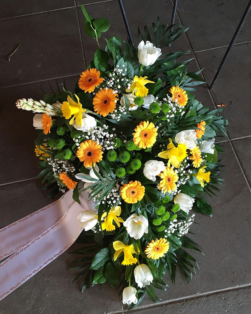 Frischblumenbukett in Tropfform mit gelben Germini, weißen Tulpen, grünen Santini, gefüllt mit weißem Schleierkraut.
