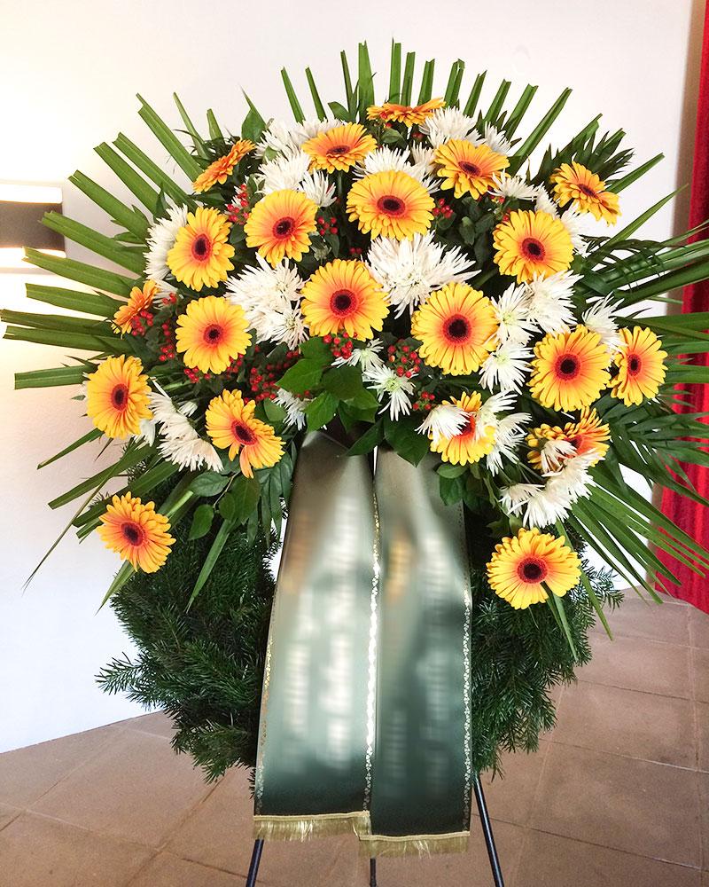 Trauerkranz mit gelben Gerbera und weißen Chrysanthemen gefüllt.