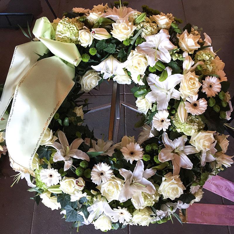 Trauerkranz mit weißen Germini, weißen Rosen, weißen Lilien, gefüllt mit grünen Hortensien.