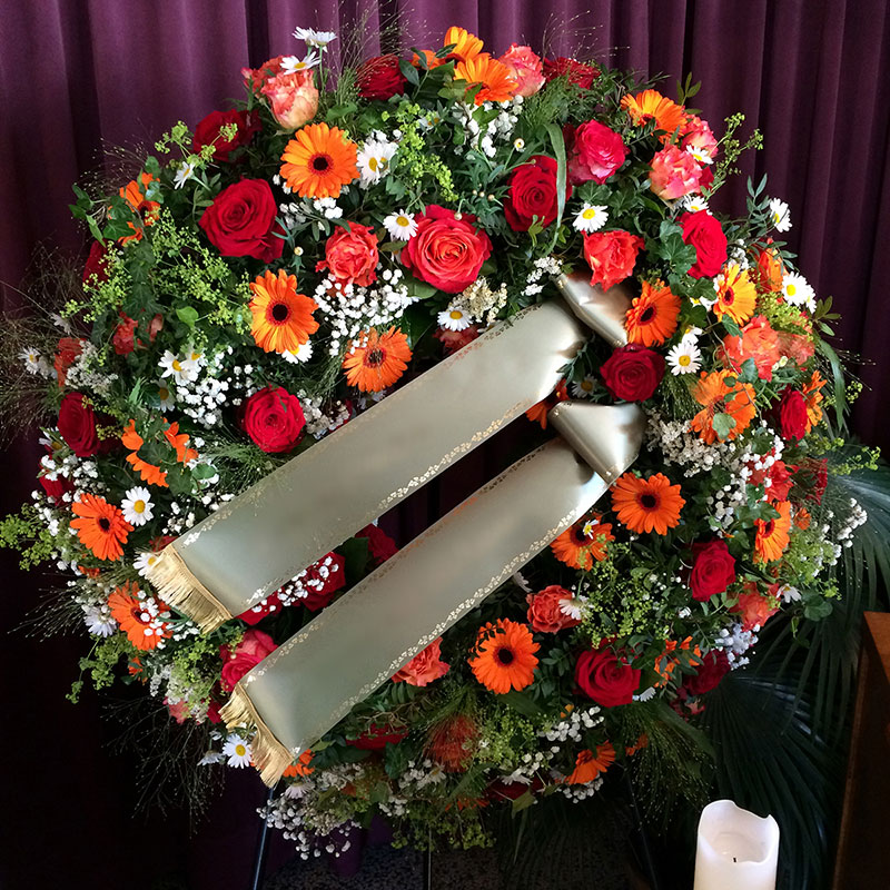 Trauerkranz mit orangen Germini, roten Rosen, weißen Margeriten und weißem Schleierkraut.