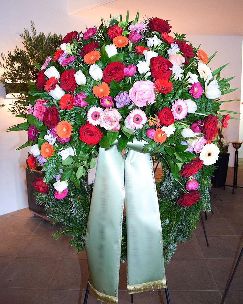 Trauerkranz mit bunten Germini, bunten Rosen, bunten Tulpen und gemischtem Grün.