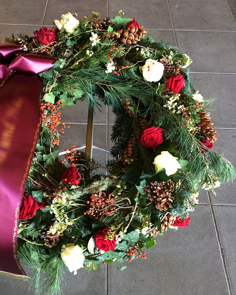 Waldkranz rund mit weißen und roten Rosen, mit verschiedenen Zapfen und gemischtem Grün.