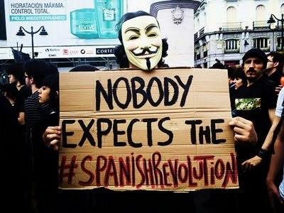 Un indignado con la máscara de Guy Fawkes sostiene una pancarta en la que se lee: Nobody expects the #SpanishRevolution