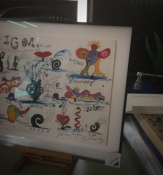 Plakat von Jean Tinguely mit Widmung, erhöht aufgelegt auf hellem Museumskarton mit Schattenwurf