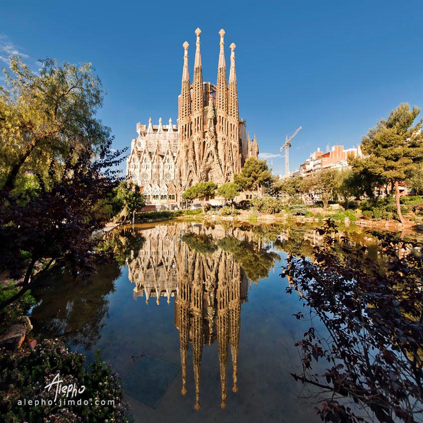 Vista completa de la Sagrada Familia con reflejo en espejo de agua