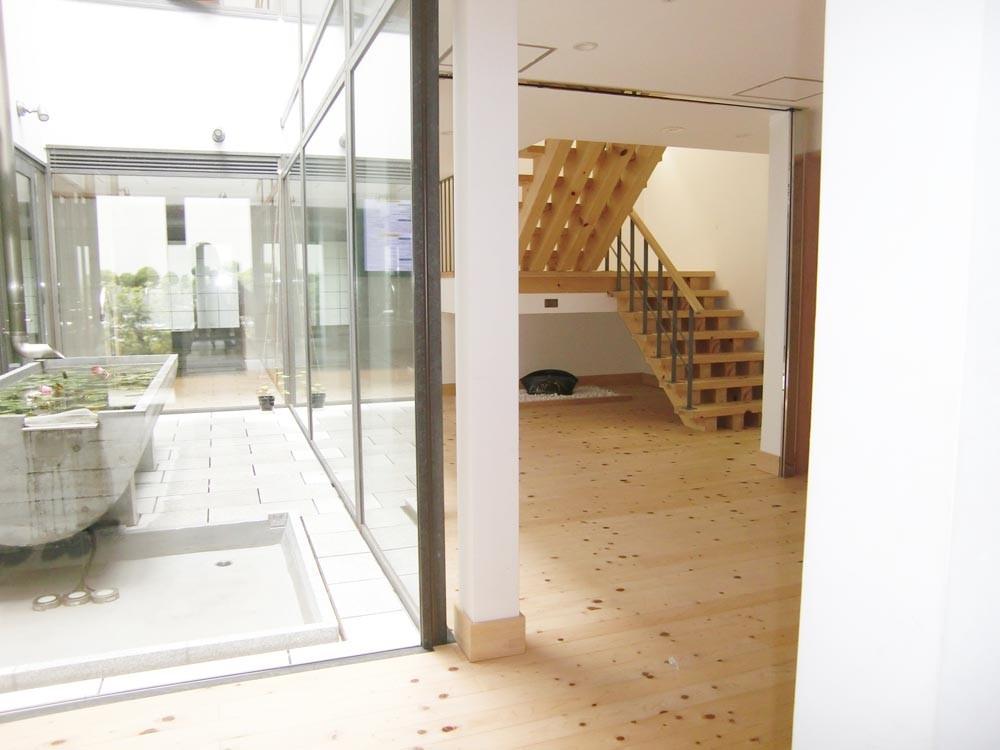 1階玄関から吹き抜けビオトープを望む。階段下の陶器 「和」宮本 博