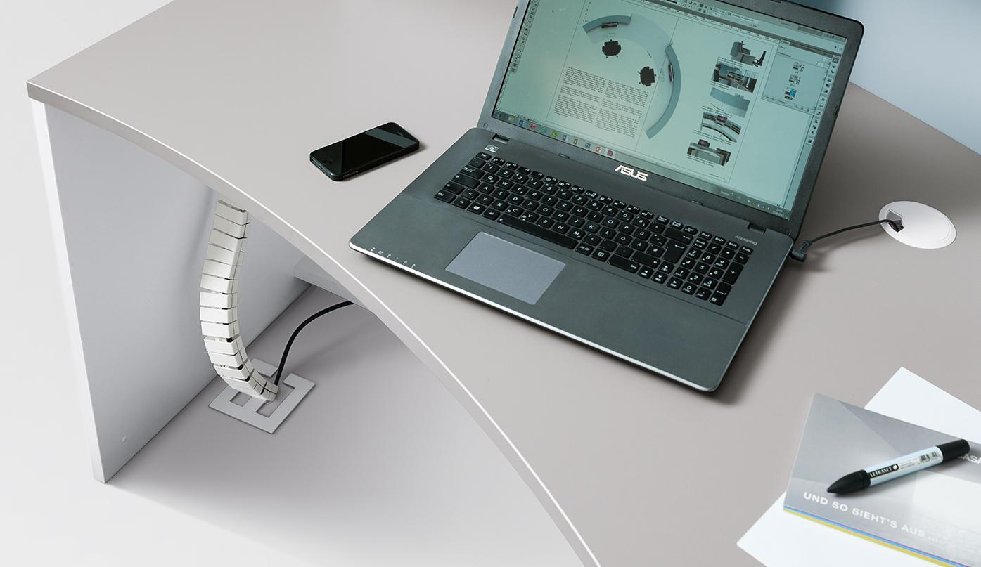 Optional ist eine Kabelkette für die senkrechte Elektrifizierung unterhalb der Tischplatte montierbar. Kabeldurchlässe in der Tischplatte sorgen für die notwendige Stromzufuhr.