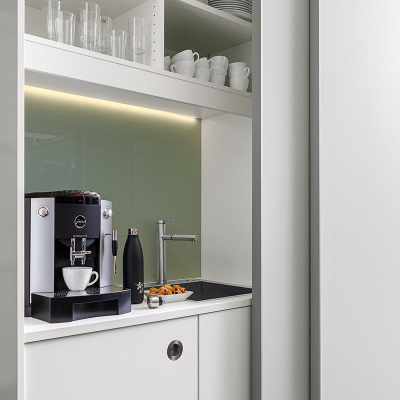 Die weißlackierte Glasrückwand inklusive LED-Beleuchtung gehört zum Standardlieferumfang.