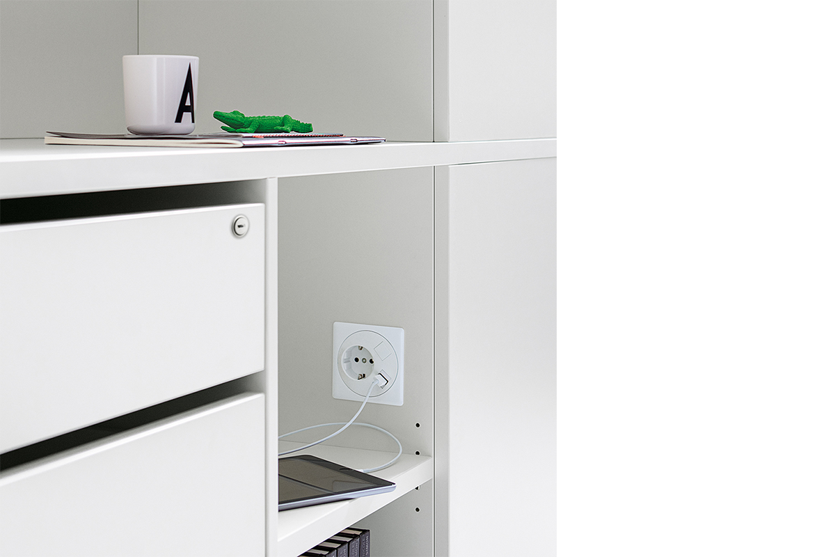 The side cabinets can optionally be fitted with sockets to provide charging stations for digital media.