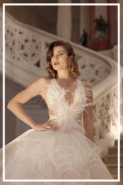 Braut in einem extravaganten Brautkleid auf einer romantischen Wendeltreppe