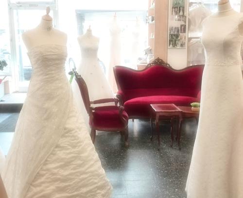 Brautmode Essen - Empfangsbereich mit romantischer Sitzgruppe und dekorierten Puppen mit Brautkleidern