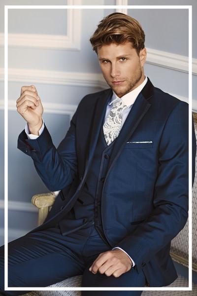 Bräutigam im blauen Anzug mit festlicher Weste, sitzend