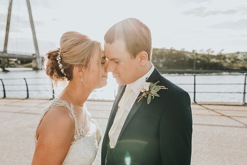 bride and groom with their heads together during the sun set