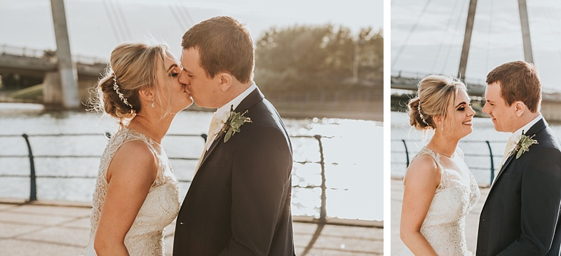 Sunset wedding portraits showing bride and groom kissing on the marine lake