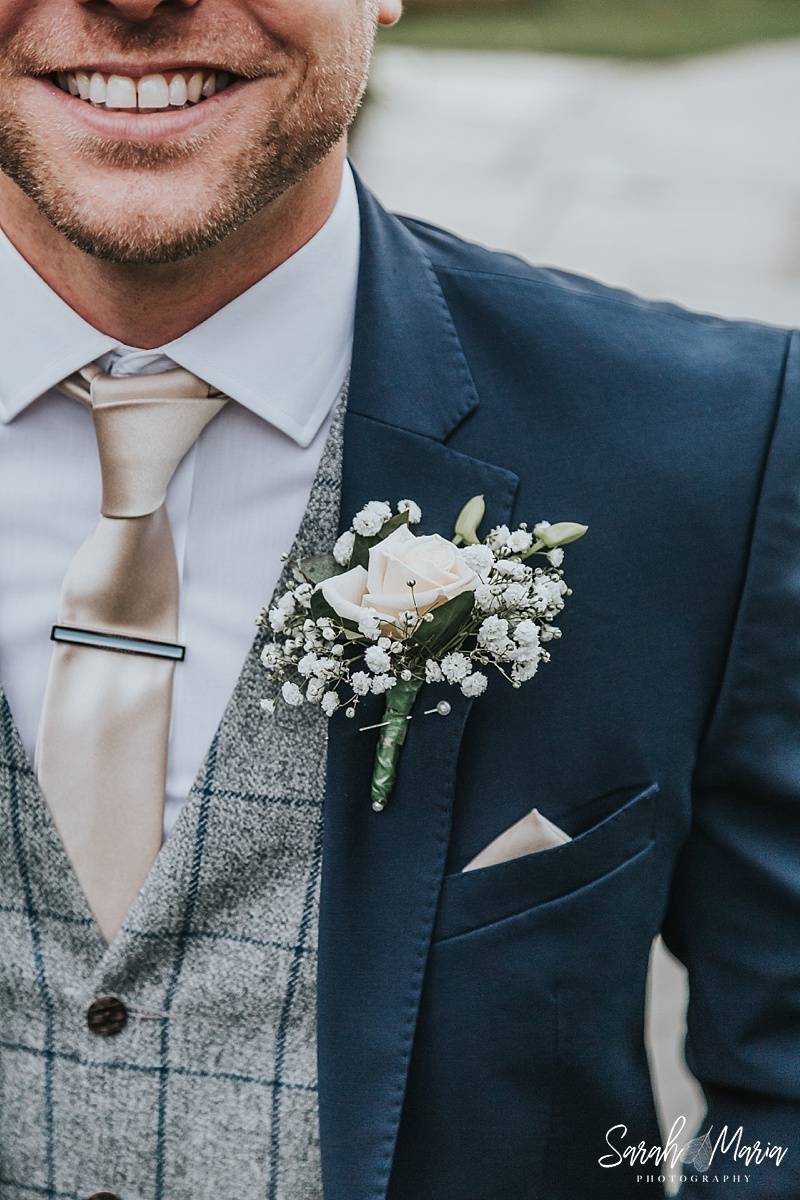 Grooms boutonniere featuring a rose and gypsophila