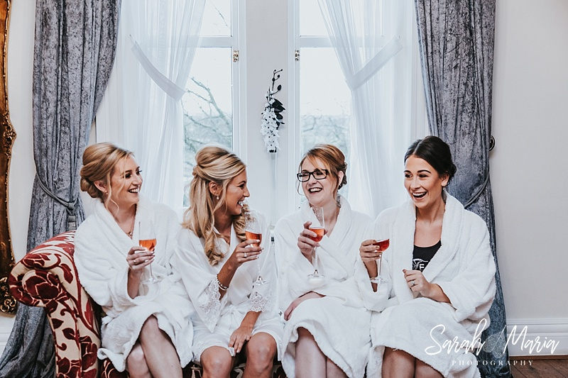 bride with her bridesmaids laughing whilst in bathrobes drinking champagne