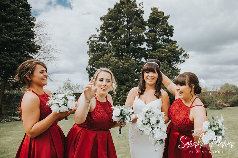 candid portrait of a bride and her bridesmaids. all laughing holding flowers in reddresses
