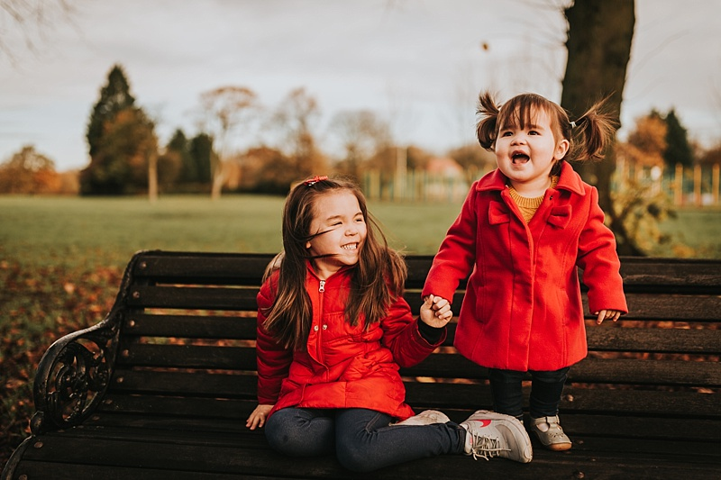 sisters having fun at the park during autumn in lancashire