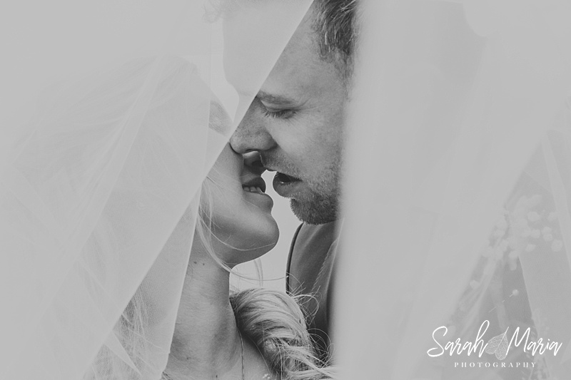 bride and groom portrait looking through a veil in black and white