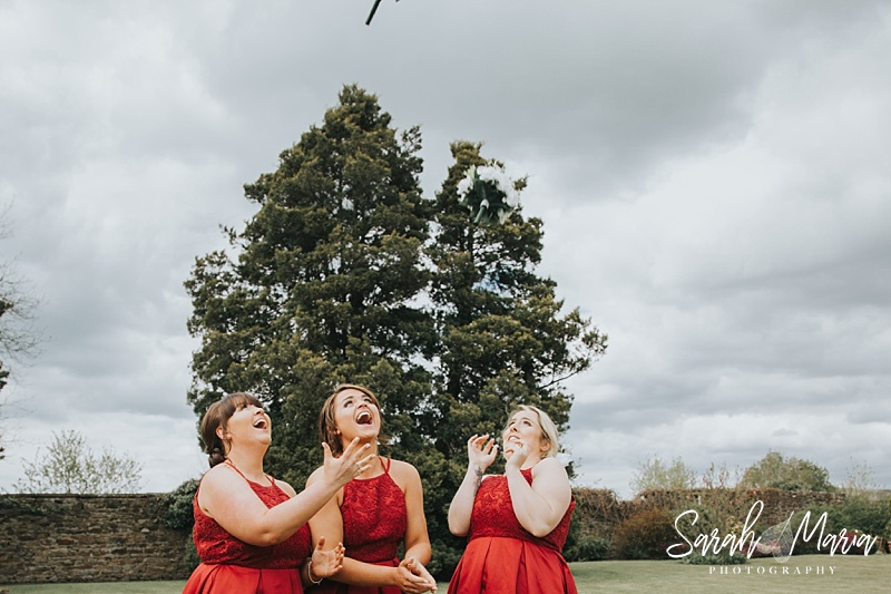 funny photo of bridesmaids throwing their bouquets up in the air