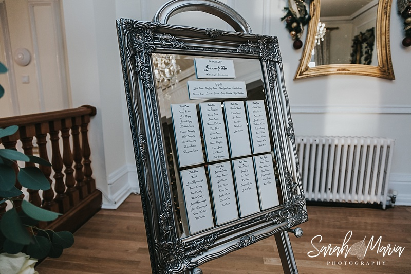 a wedding seating plan on a vintage pewter mirror