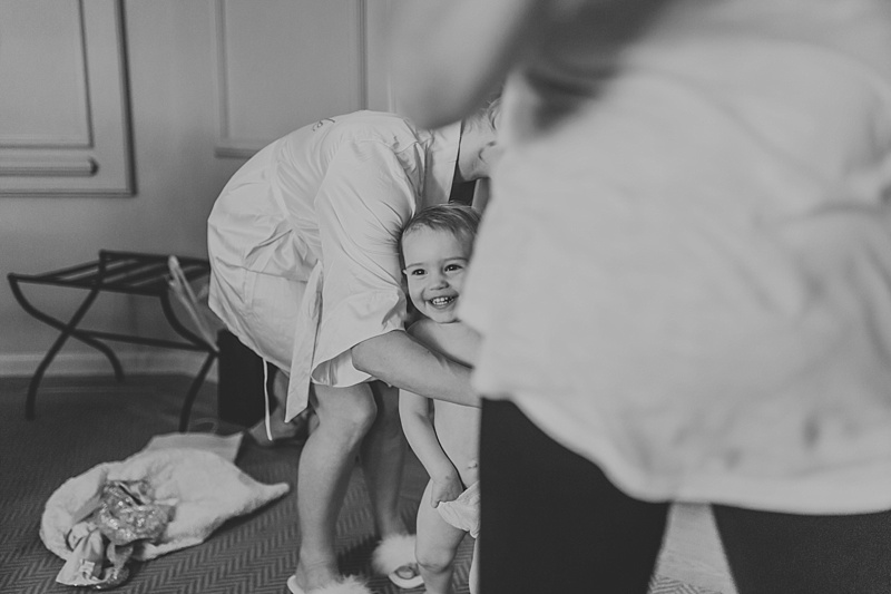 cheeky little flower girl laughing as her mum is trying to dress her