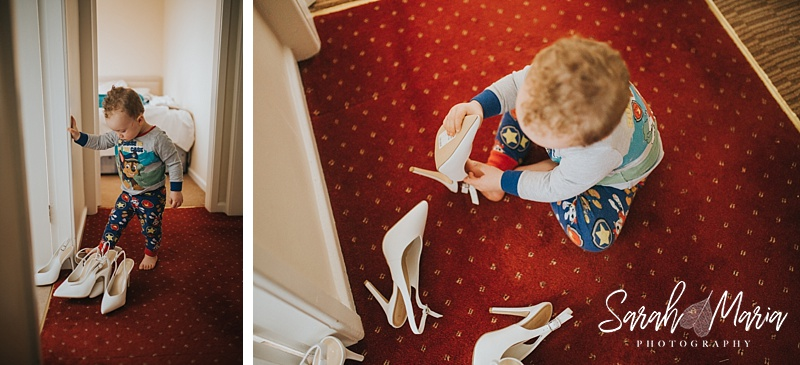 a little boy trying to put on a pair of high heeled shoes