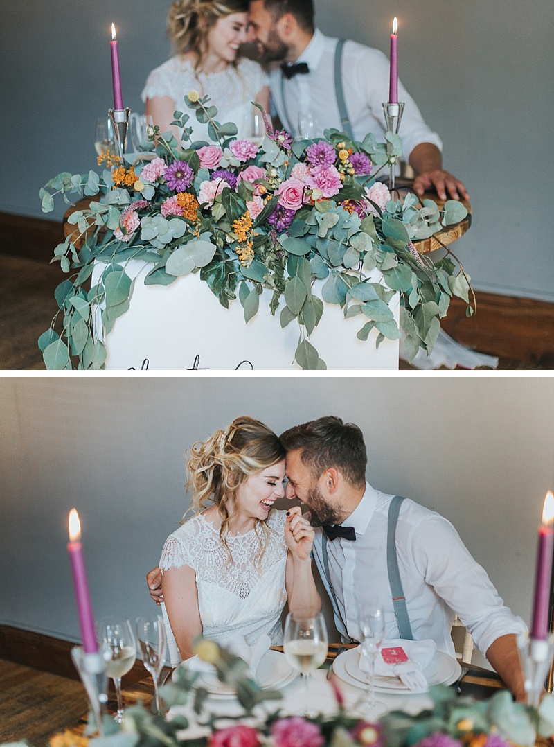 a bride and groom sat at a sweetheart table
