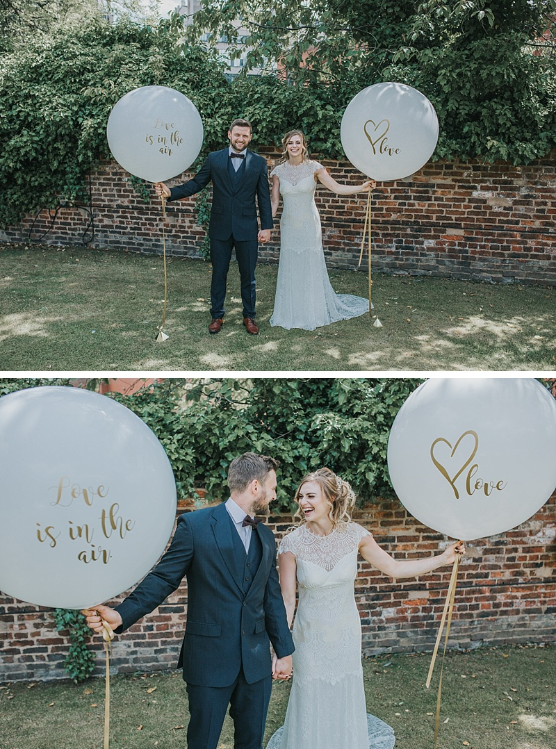 bride and groom with giant wedding balloons