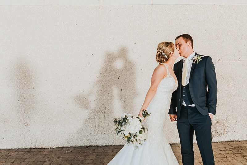 Cute portrait of a bride and groom kissing with their shadows behind them on a wall
