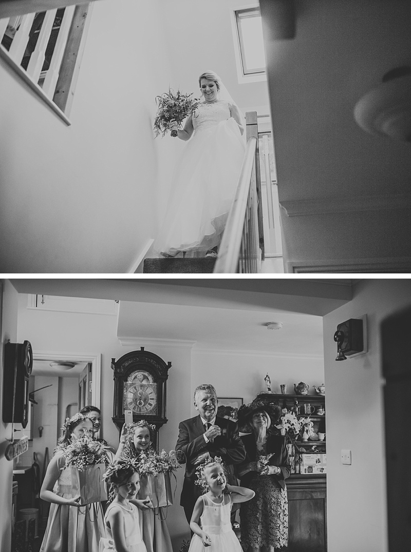 bride walking down the stairs on her wedding day whilst her parents and bridesmaids look with excitement