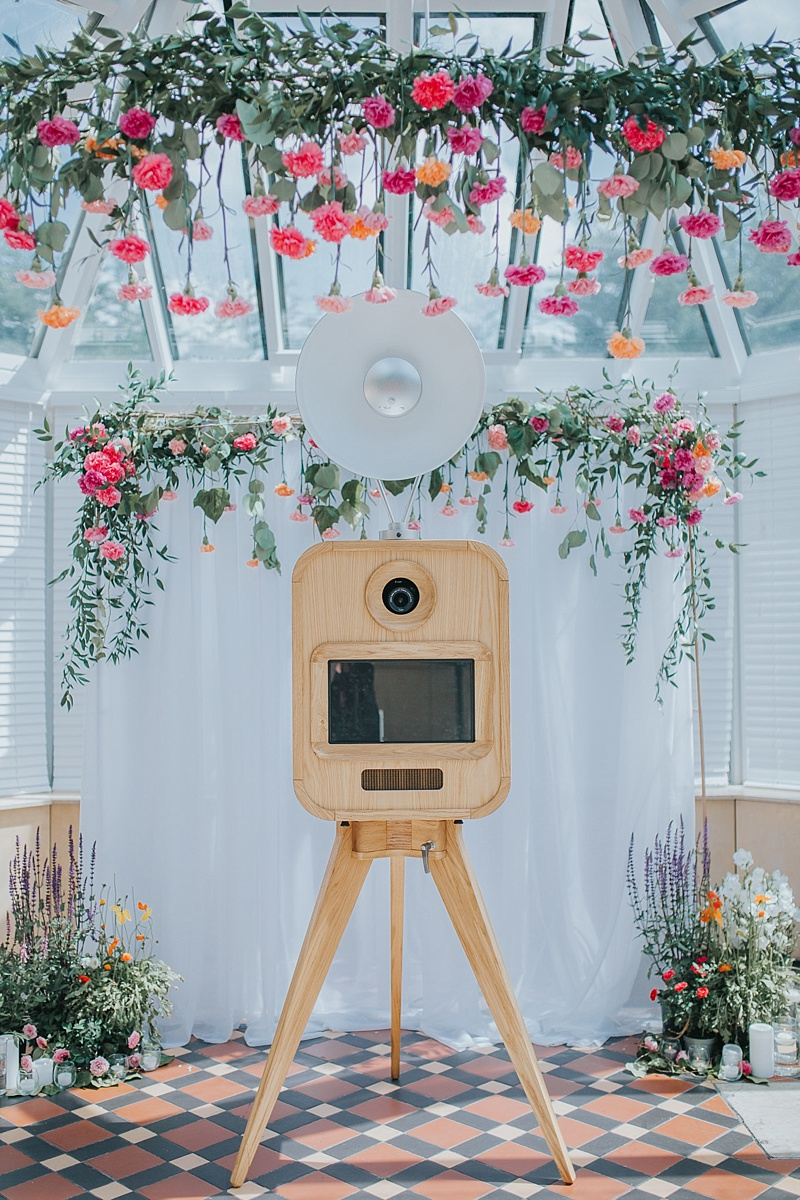 viva la booth photobooth infront of a wedding arbour