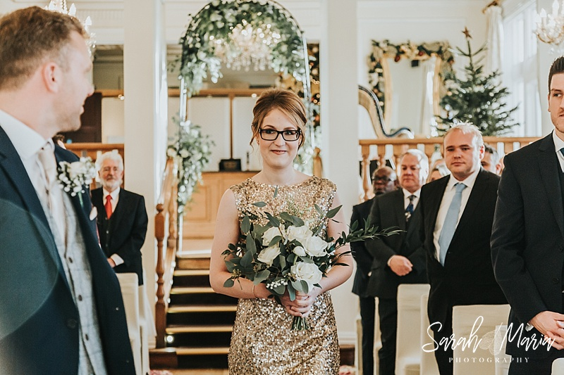 bridesmaid in a gold dress walking down the aisle