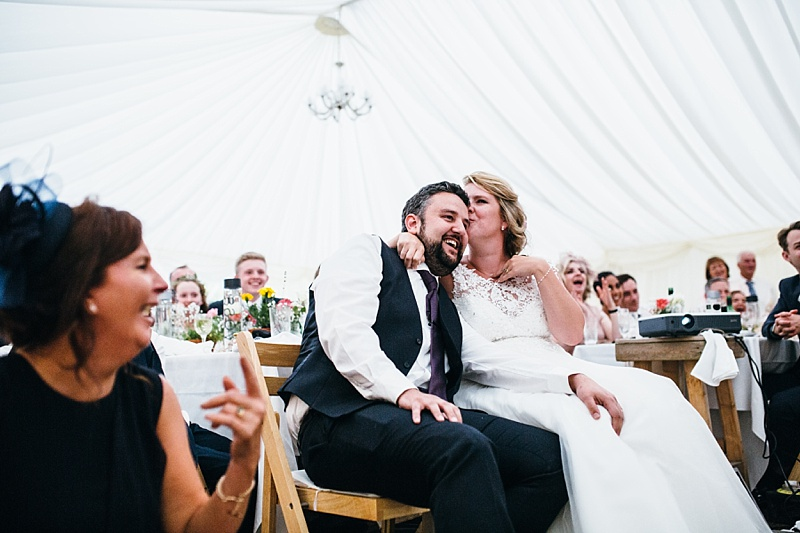 sweet moment between a bride and groom where she is kissing his head