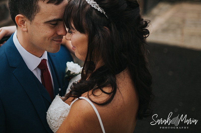 an intimate portrait of a bride and groom holding their heads together