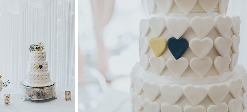 wedding cake with fondant hearts. Two of the hearts are coloured yellow and blue