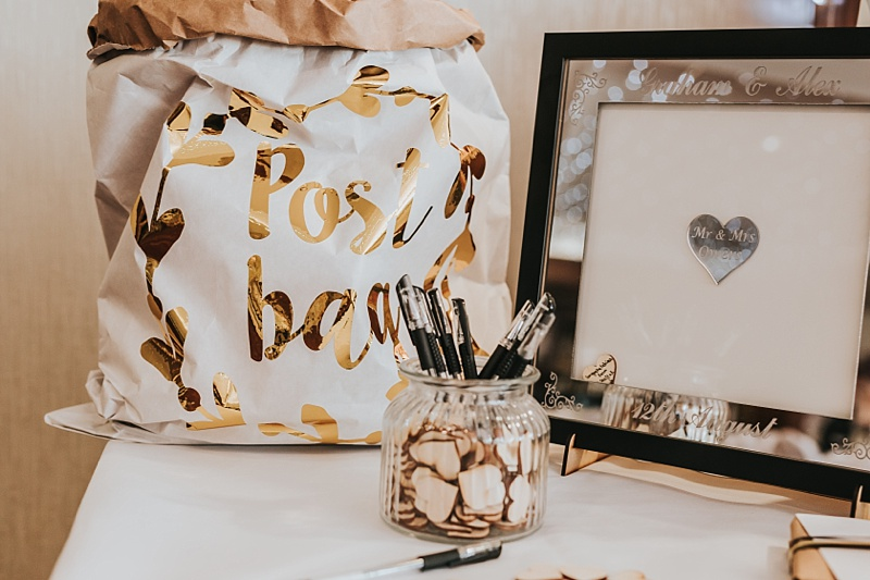 Guest book idea for a wedding with a paper post bag and gold foil writing