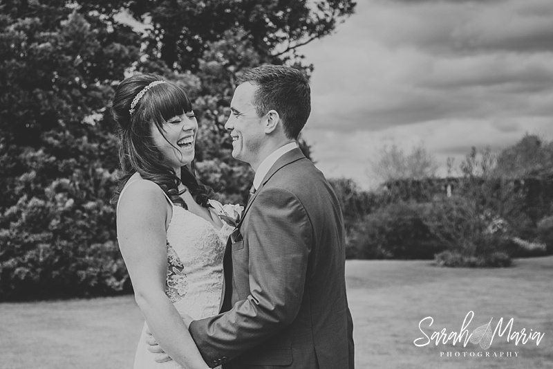 natural black and white portrait of a bride and groom. the bride is laughing