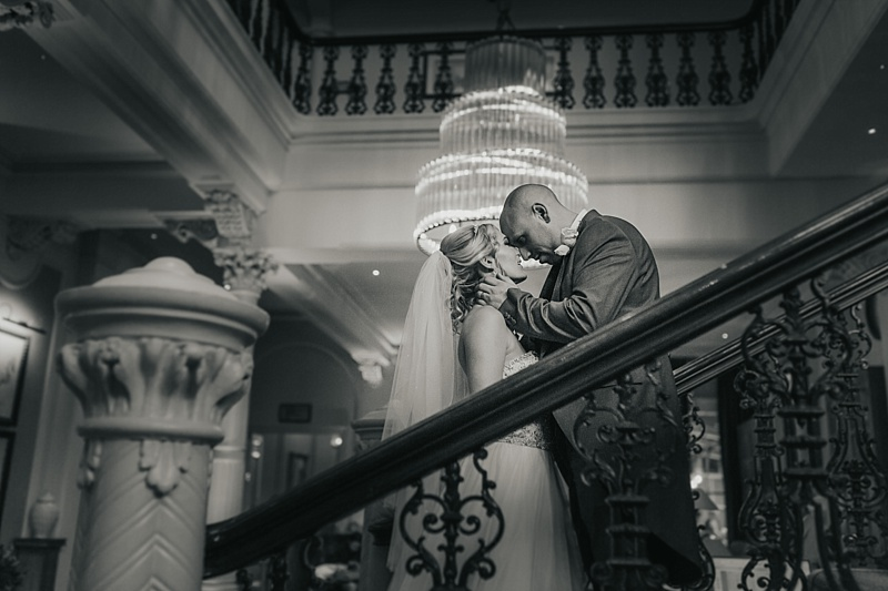 black and white picture of a bride and groom on a grand staircase