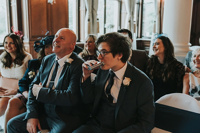 cheeky guest having a drink from a hip flash at a wedding
