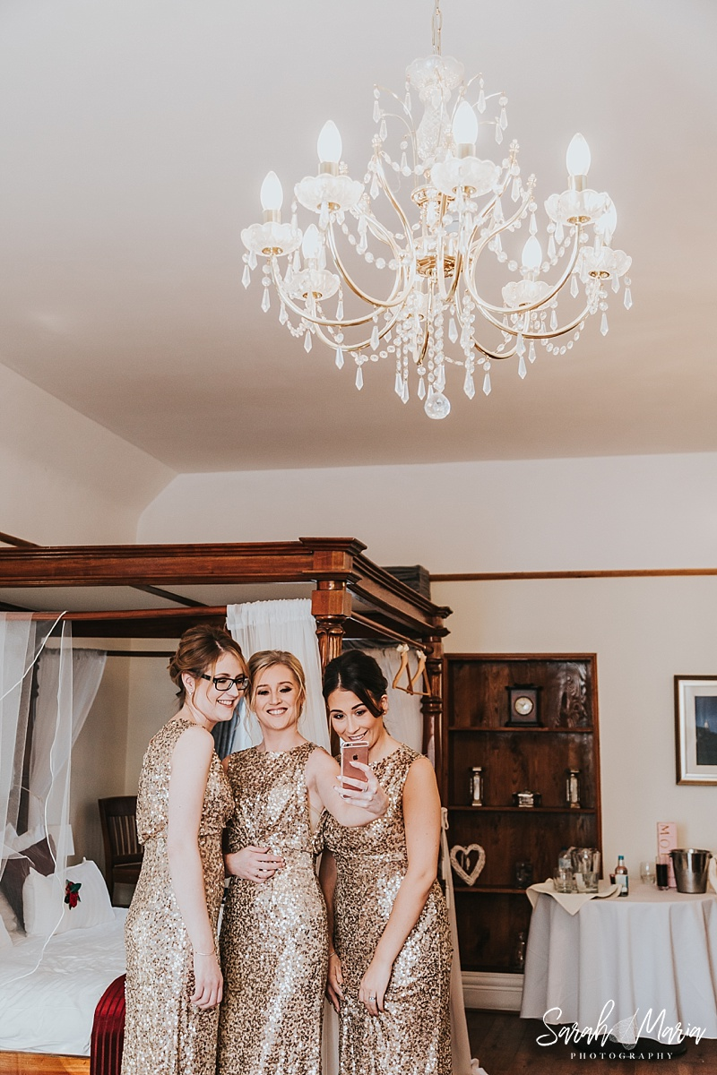 bridesmaids taking a selfie in gold sequin dresses